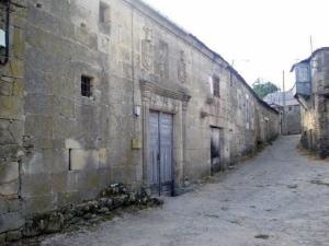 Exterior del Pazo de Fradelo, con la puerta principal de entrada y los blasones en la parte superior.